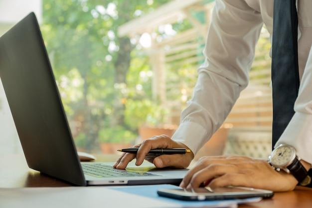 Bussinessman trabalhando no computador portátil no escritório.