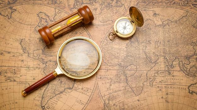 Bússola antiga, lupa e relógio de areia no mapa vintage