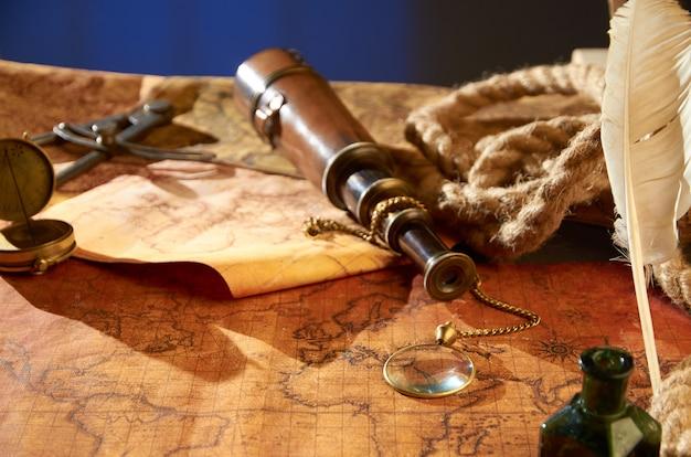 Bússola com cachimbo vergonhoso e caneta com tinta deitado no mapa antigo
