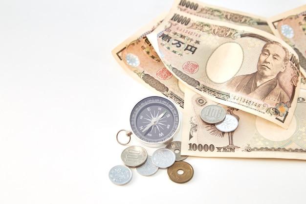 Bússola com notas de iene japonês e moeda de iene japonês em fundo branco