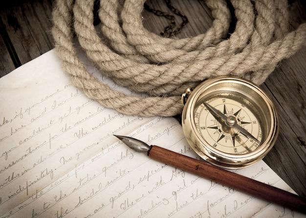 Bússola, corda, caneta e carta em um papel velho em um fundo de madeira fechar