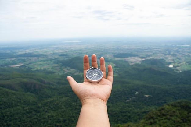Bússola de mão com vista para a floresta, trekking e perdido no conceito de floresta. foco suave,