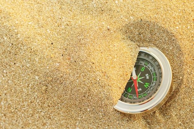 Bússola de prata magnética na areia