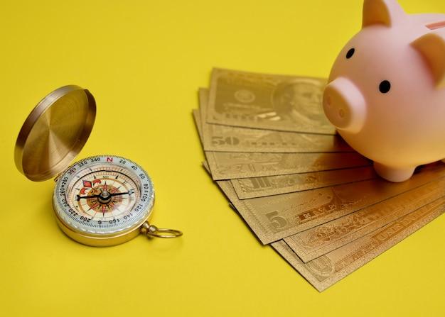 Bússola, dólares de ouro e cofrinho em fundo amarelo