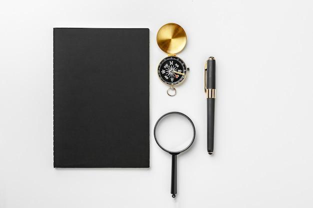 Bússola dourada com caneta e bloco de notas preto close-up sobre uma mesa