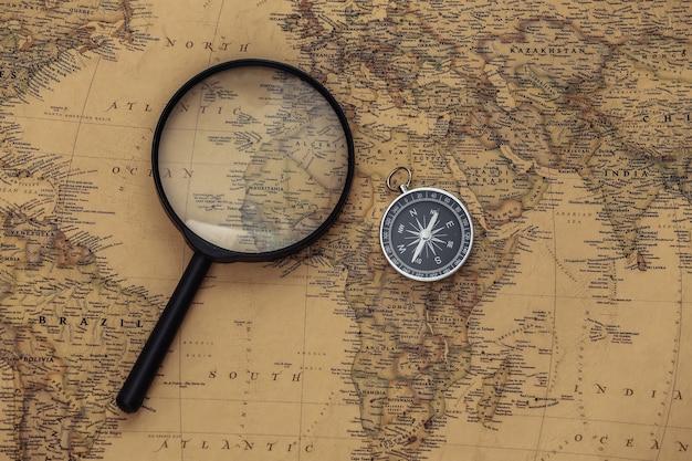 Bússola e lupa no mapa antigo. viagem, conceito de aventura