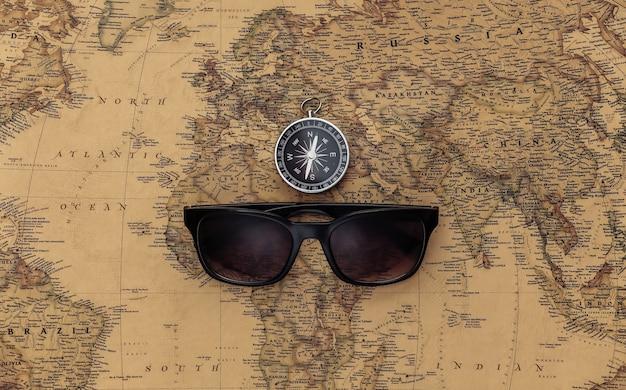 Bússola e óculos de sol no mapa antigo. viagem, conceito de aventura