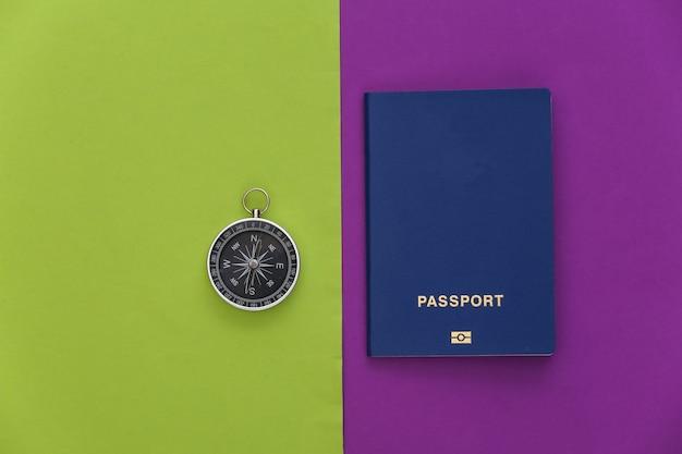 Bússola e passaporte em fundo verde roxo. vista do topo. conceito de viagens do minimalismo. postura plana