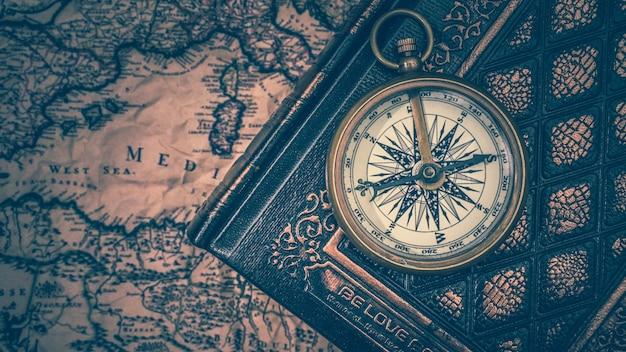 Bússola em livro antigo e mapa