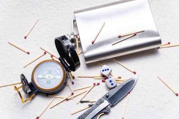 Bússola, frasco, faca e fósforos espalhados em um fundo branco