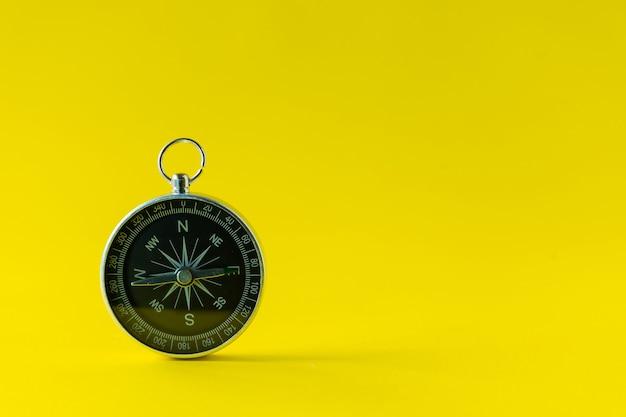 Bússola isolada em fundo amarelo conceito de objetivo de vida bússola apontando o caminho