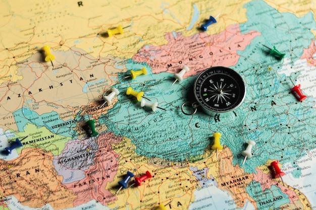 Bússola magnética e alfinetes no mapa.