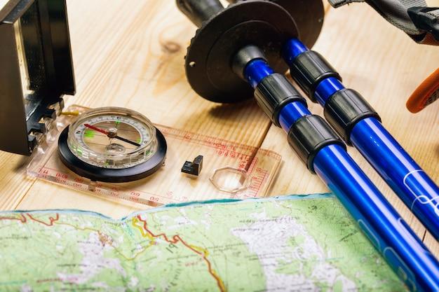 Bússola, mapa, bastões de trekking e mochila em fundo de madeira