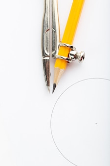 Bússola metálica isolada com lápis, uma vista superior em branco
