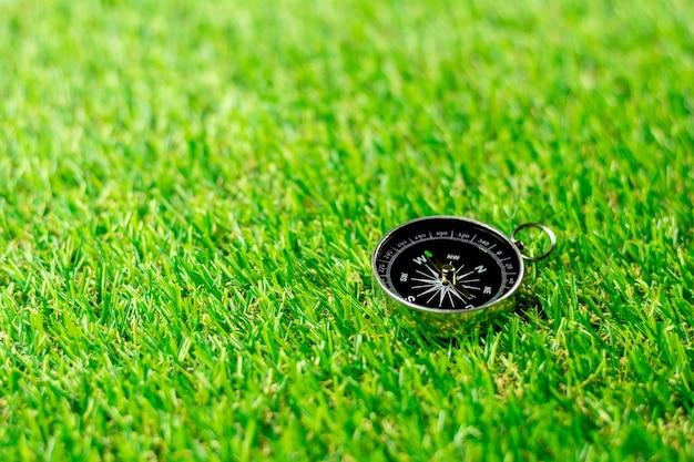 Bússola no gramado verde da manhã.