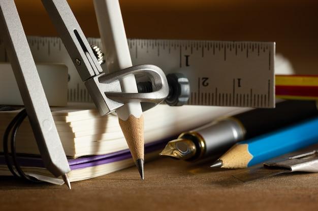 Bússola para desenho e estacionário na mesa de madeira.