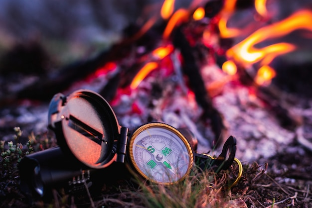 Bússola perto de uma fogueira em um acampamento turístico