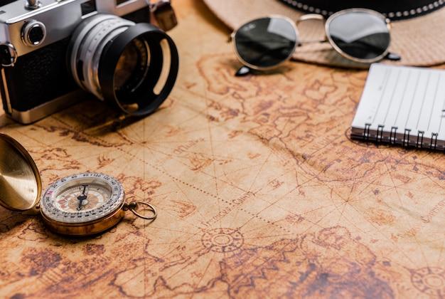 Bússola vintage e câmera no mapa para planejamento de viagens