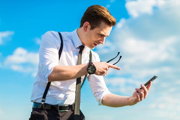 Busunessman atraente na camisa branca, gravata, aparelho e óculos de sol fica na escada do telhado