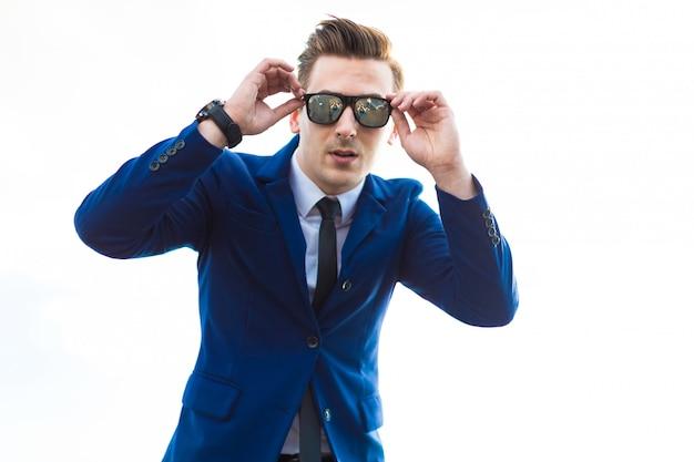Busunessman jovem atraente de terno azul e óculos de sol fica no telhado