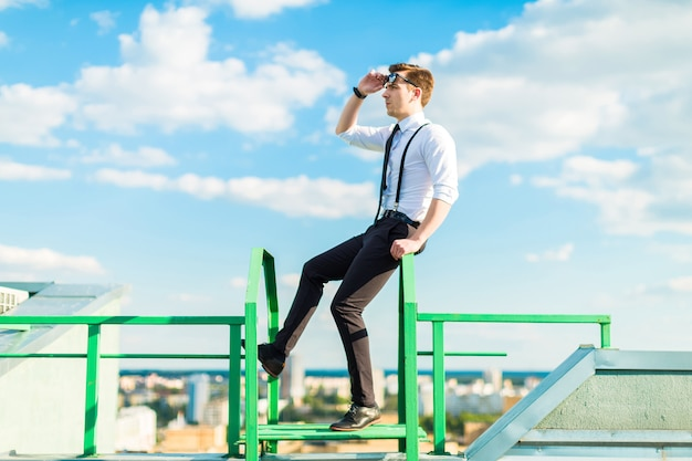 Busunessman jovem de camisa branca, gravata, aparelho e óculos de sol fica na escada do telhado