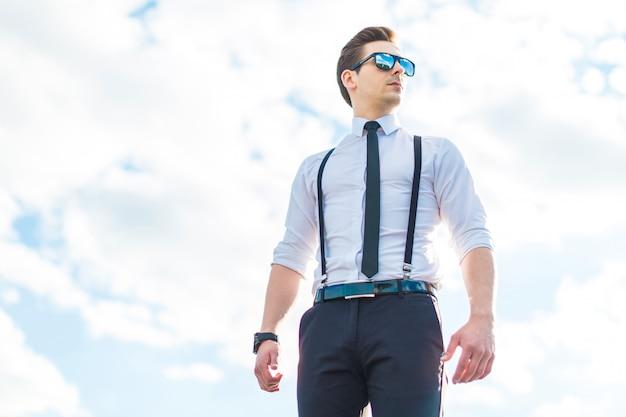 Busunessman jovem sério na camisa branca, gravata, aparelho e óculos de sol fica no telhado