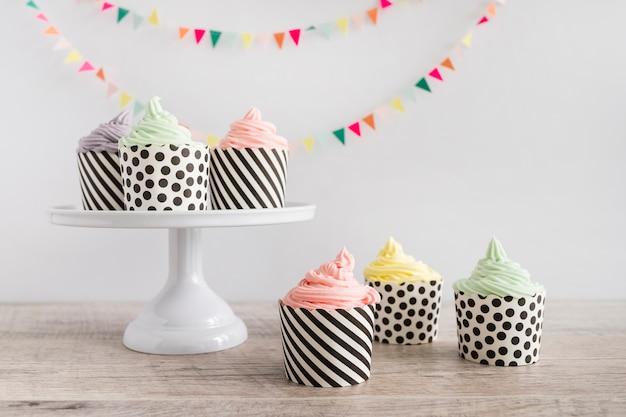 Buttercream de cor pastel cupcakes na frente da flâmula