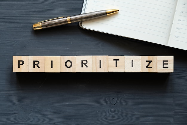 Buzzword empresarial moderno - priorizar. vista superior na mesa de madeira com blocos. vista do topo.