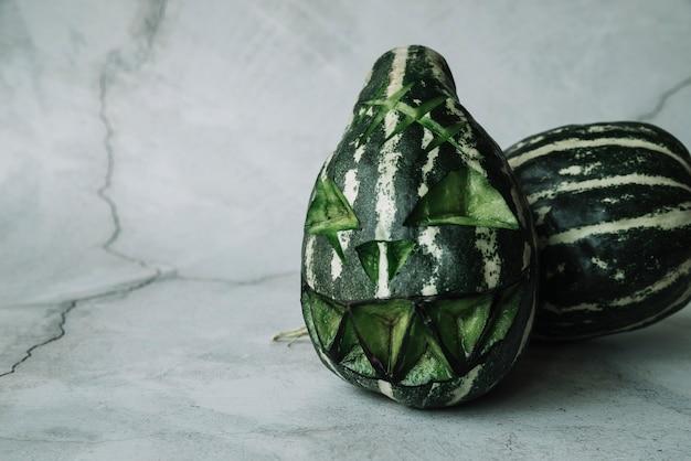 Cabaças verdes com rosto assustador esculpido