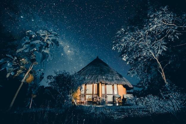 Cabana aconchegante sob um céu estrelado. fundo de conto de fadas