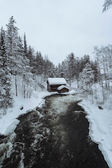 Cabana coberta de neve à beira do rio no parque nacional oulanka, finlândia