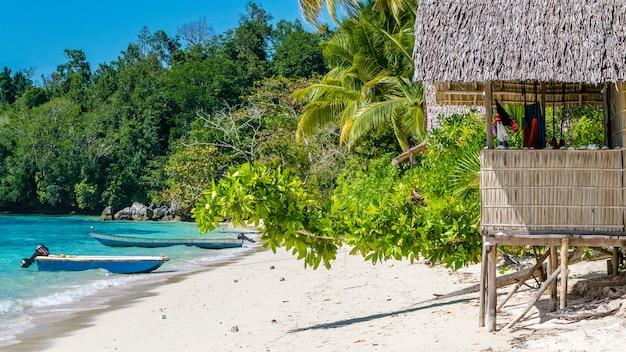 Cabana de bambu sob palmeiras de uma casa de família na ilha gam, papuã ocidental, raja ampat, indonésia.