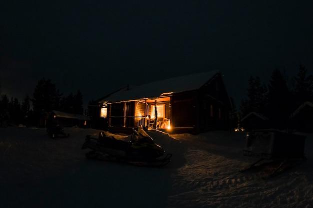 Cabana de madeira na neve à noite