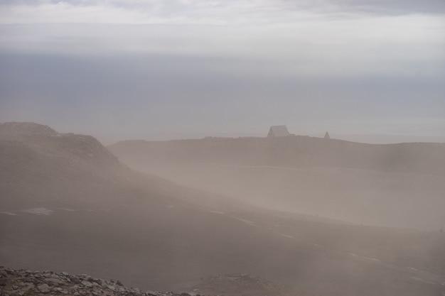 Cabana islandesa na paisagem vulcânica durante forte tempestade de cinzas na trilha fimmvorduhals ic ...