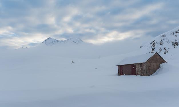 Cabana pequena e montanha em uma manhã gelada