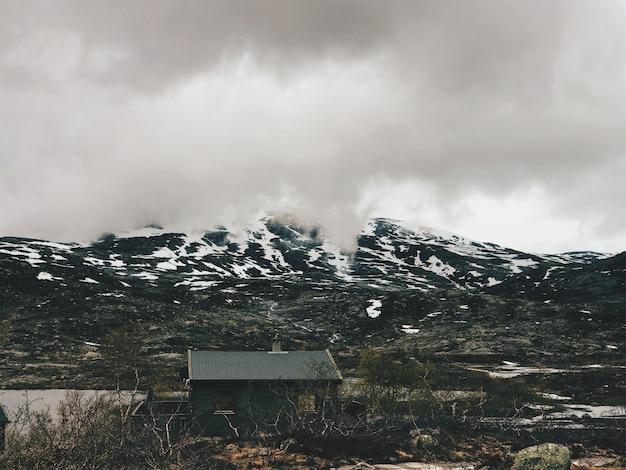 Cabana solitária fica diante das montanhas cobertas de neve
