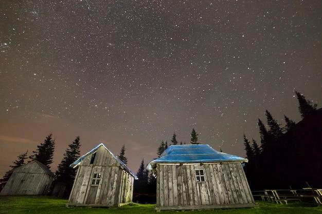 Cabanas de madeira velhas do pastor nas montanhas que cancelam sob o céu estrelado.