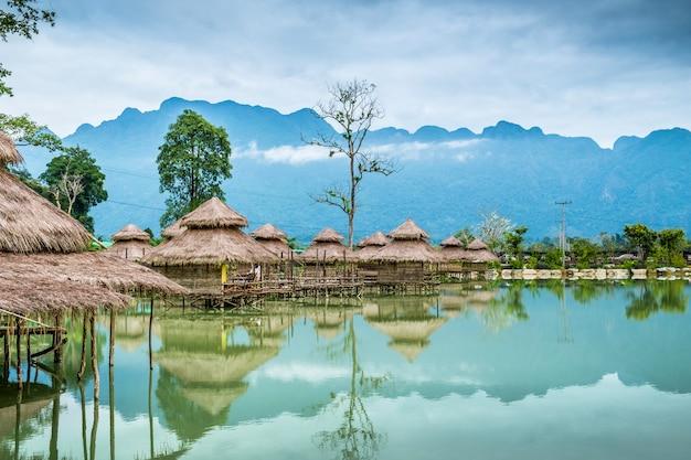 Cabanas no lago com fundo de montanhas.