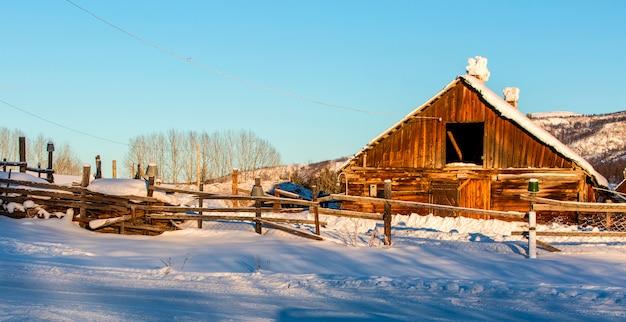 Cabanas rústicas cobertas de neve na floresta no inverno