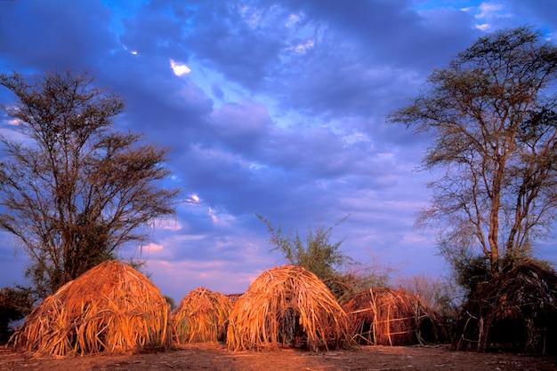 Cabanas tradicionais na aldeia mursi em face da tempestade que se aproxima