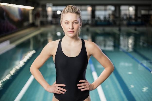 Cabe a mulher com as mãos nos quadris na piscina