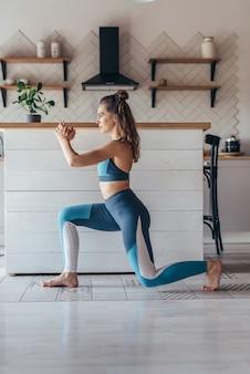 Cabe a mulher malhando em casa. exercício de estocadas de treinamento de perna.