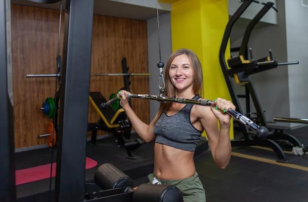 Cabe a mulher no exercício de sportswear com máquina de peso de exercício no ginásio. treinamento de garota atraente. fitness, conceito de esporte