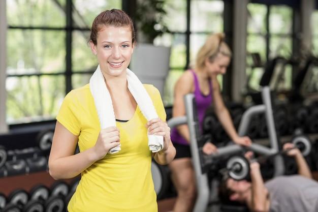 Cabe a mulher posando com os braços cruzados no ginásio