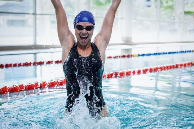 Cabe a mulher triunfando com os braços erguidos na piscina