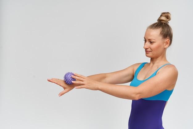 Cabe mulher em roupas esportivas com bola de massagem nas mãos dela.
