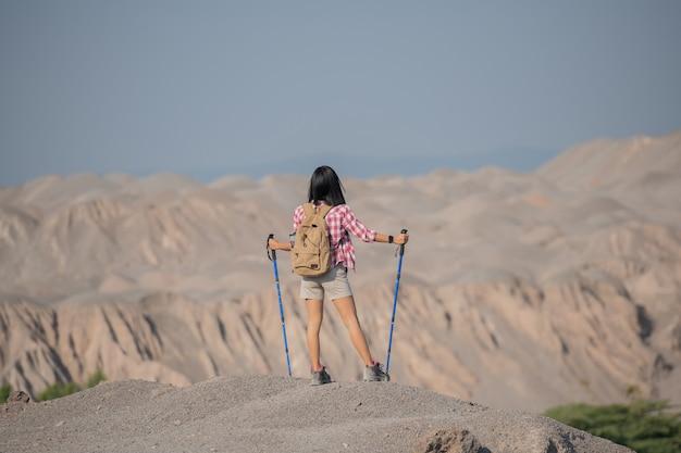 Cabe mulher jovem, caminhadas nas montanhas de pé sobre uma crista rochosa do cume com mochila e poste, olhando a paisagem.