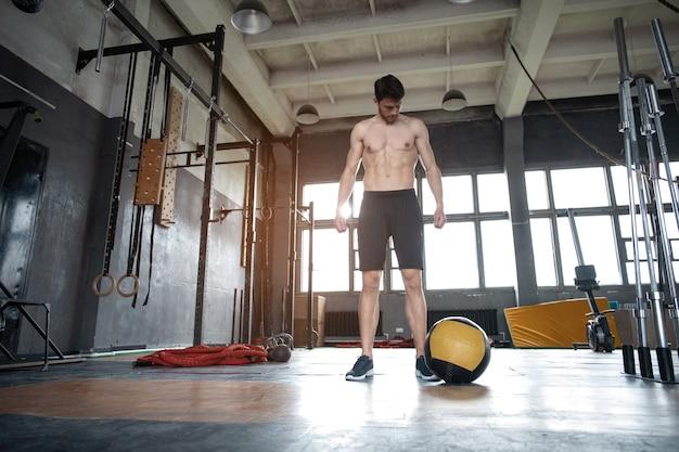 Cabe o homem jogando medicine ball fazendo ball slam contra o chão do ginásio ou exercícios de treino da parte superior do corpo de imprensa de ombro. treinamento cruzado no centro de fitness.