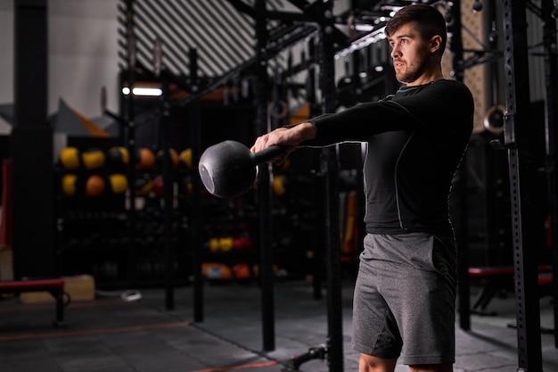 Cabe o homem levantando o sino da chaleira durante o treinamento na academia. homem fazendo levantamento de peso com kettlebell. treinamento cross fit, esporte, conceito de estilo de vida saudável