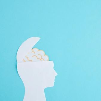 Cabeça aberta de recorte de papel branco com cérebro em pano de fundo azul